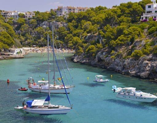 Detalle de Cala Pi, Mallorca con bañistas al fondo y embarcaciones amarradas